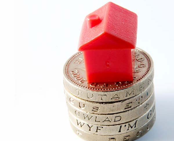 Small red house stacked on top of pound coins